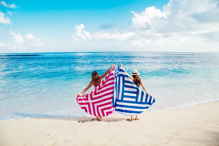 Couple of women covering their body with a beach towel