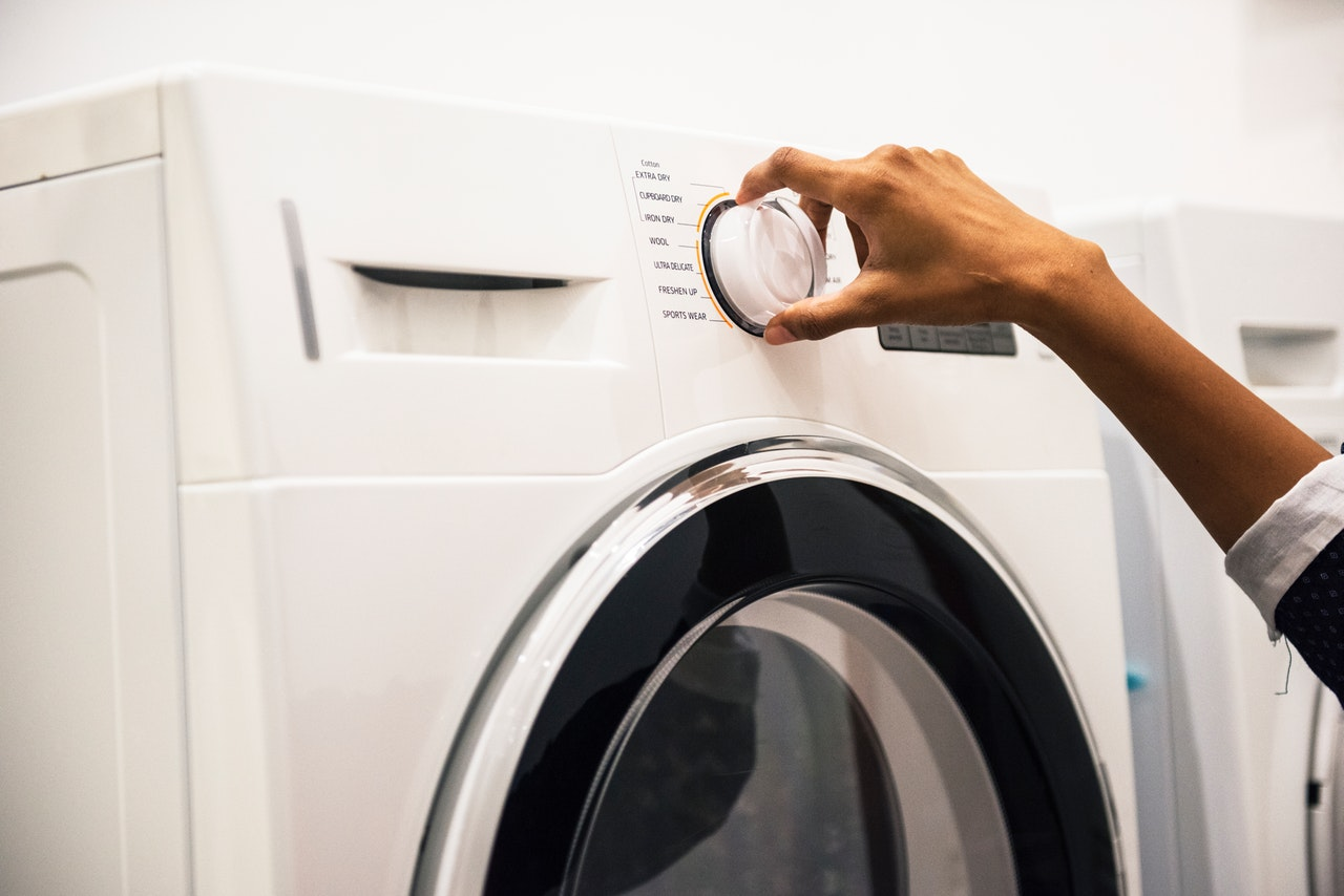 Person adjusting a knob on a front load washer and dryer